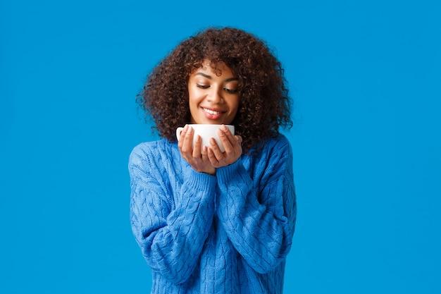 Gezelligheid, huis en vakantie concept. ontspannen sensueel en opgetogen, glimlachende tedere afro-amerikaanse vrouw met krullend haar, kijkend naar heerlijke warme thee, koffie drinken uit een beker, grijnzend