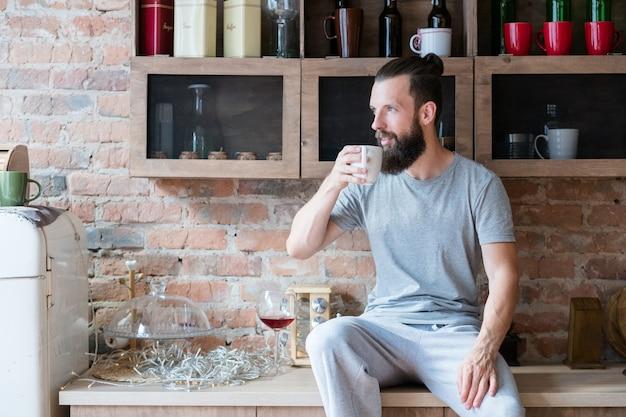 Gezelligheid in de ochtend. eenzaamheid thuis. nieuwe dag. man met kop warme drank zittend op het aanrecht en zijwaarts op zoek.