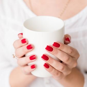 Gezelligheid in de ochtend. warme drank verwarmende verzorgde handen. ontspannen met een kopje favoriete drank.