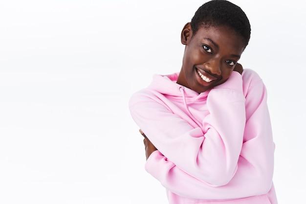 Gezelligheid, tederheid en schoonheid concept. schattige jonge romantische afro-amerikaanse vrouw omhelst eigen lichaam