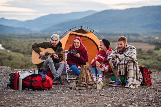 Gezelschap van jonge vrienden die een picknick bij de bergen hebben
