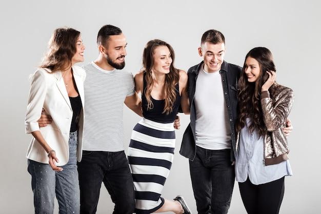 Gezelschap van meisjes en jongens in modieuze vrijetijdskleding praten op een witte achtergrond in de studio.