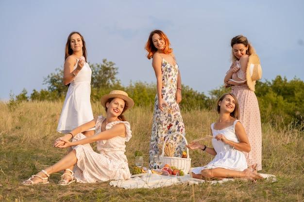 Gezelschap van stijlvolle gelukkige vriendinnen plezier op outdoor retro-stijl picknickpartij