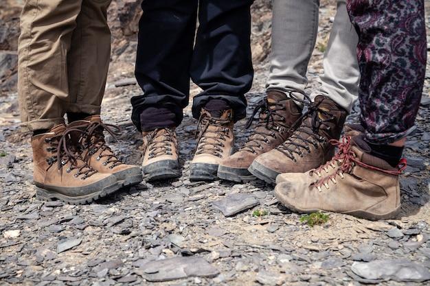Gezelschap van toeristenbenen samen in bruine trekking wandelschoenen met veters op rotsachtige klif