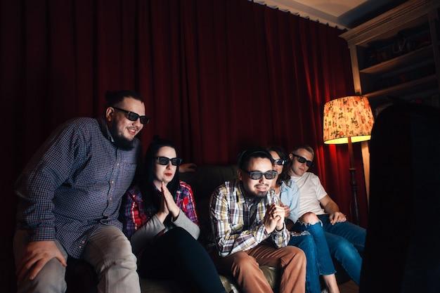 Gezelschap van vijf jonge gelukkige vrienden in 3d-bril op de bank, kijk thuis film op tv