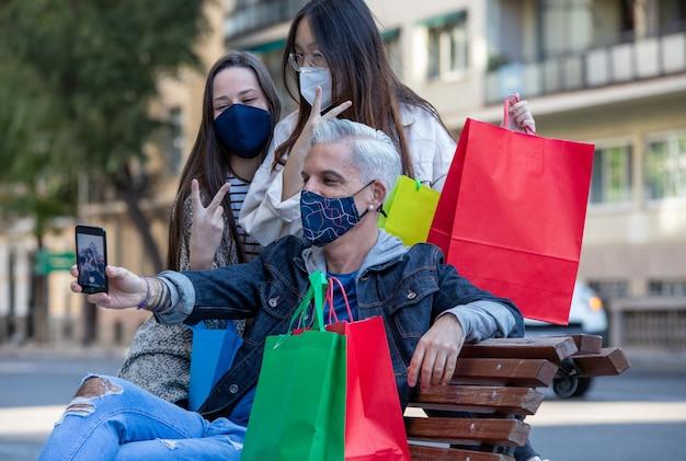 Gezelschap van vrienden in maskers selfie te nemen in de stad