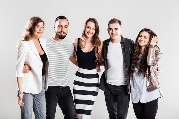 Gezelschap van vrienden in modieuze vrijetijdskleding staan samen en glimlachen op een witte achtergrond in de studio.