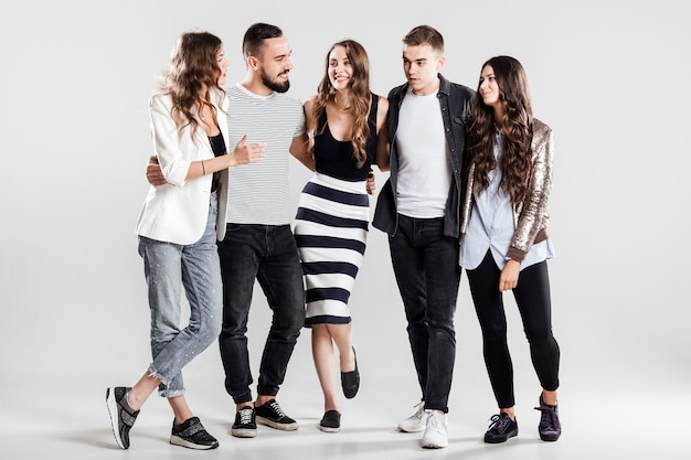 Gezelschap van vrienden in modieuze vrijetijdskleding staan samen en praten op een witte achtergrond in de studio.