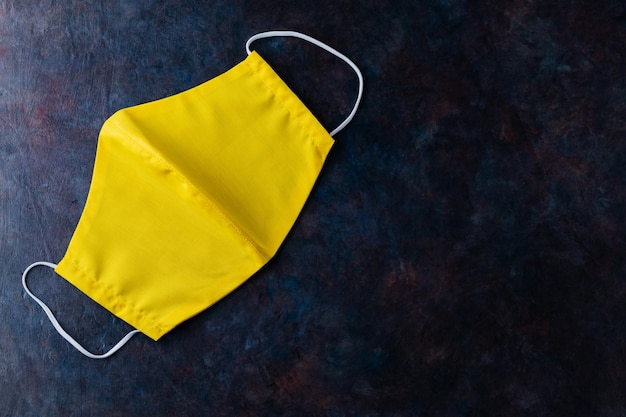 Gezicht beschermend masker. geel beschermend masker op een donkere achtergrond. bovenaanzicht. kopieer ruimte