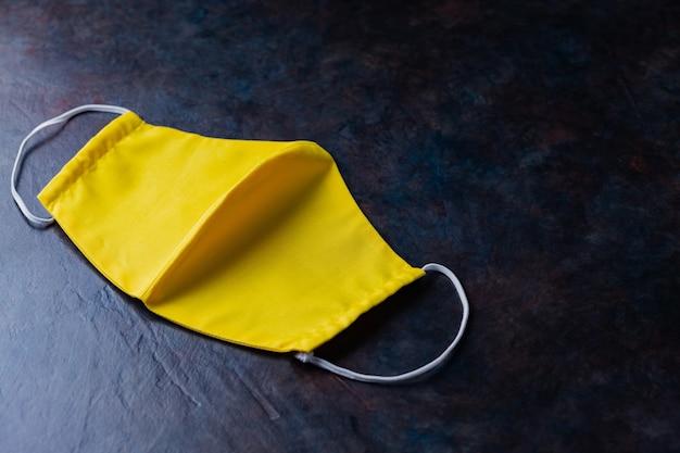 Gezicht beschermend masker. herbruikbaar antivirusmasker. geel beschermend masker. kopieer ruimte