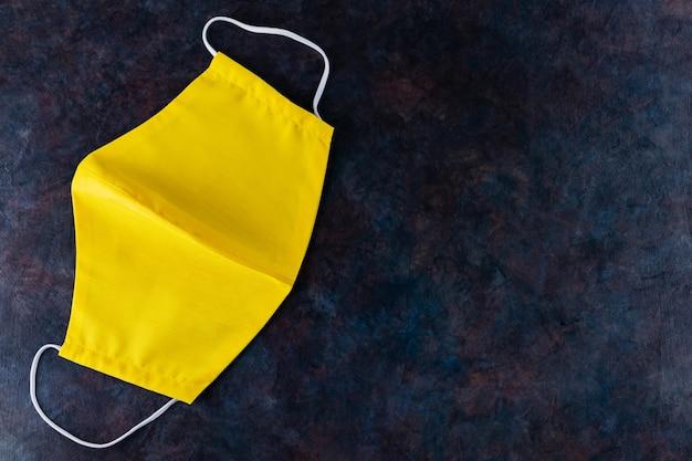 Gezicht beschermend masker. herbruikbaar antivirusmasker gemaakt van geel katoen. bovenaanzicht. kopieer ruimte