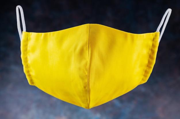Gezicht beschermend masker. herbruikbaar antivirusmasker gemaakt van geel katoen. geel beschermend masker