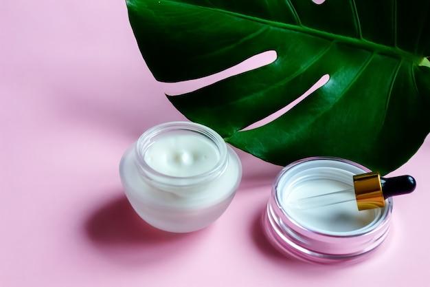 Gezicht en lichaamsverzorging concept close-up sheffler blad en eco schone cosmetica crème op roze achtergrond