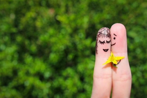 Gezicht geschilderd op vingers. de man geeft bloemen aan een vrouw.