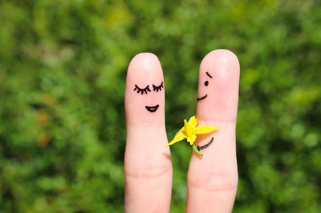Gezicht geschilderd op vingers. man geeft bloemen aan een vrouw.