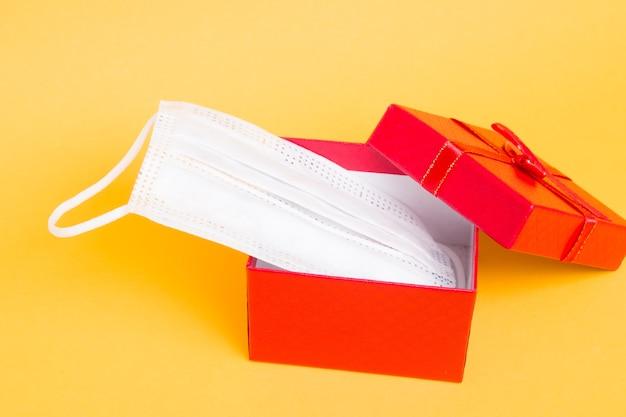 Gezicht medisch masker en rode geschenkdoos op een gele achtergrond kopie ruimte
