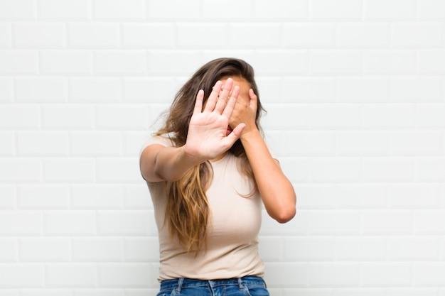 Gezicht met hand bedekken en andere hand naar voren steken om de camera te stoppen, foto's of afbeeldingen weigeren