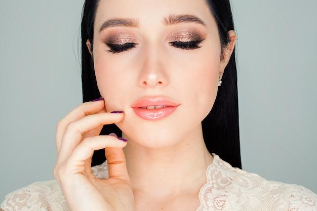 Gezicht met heldere huid, portret van een vrouw met blauwe ogen, op een witte muur. het concept van een gezichtscrème met een liftende werking of huidreiniging.