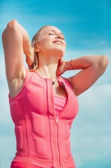 Gezicht naar de zon. taille-omhoog portret van een tevreden blanke vrouw met nat blond lang haar in een roze reddingsvest, koesterend in de zon