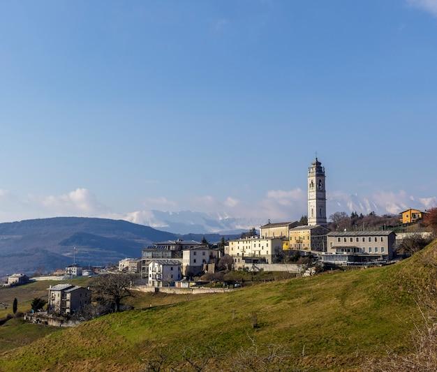 Gezicht op cerna di sant'anna d'alfaedo met de klokkentoren van de oude kerk.