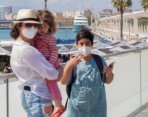 Gezicht op een gezin dat in pandemische tijden reist met maskers.