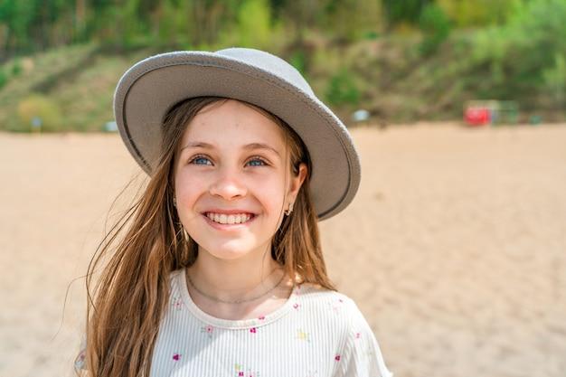 Gezicht op een klein meisje met een breedgerande hoed bij de zee op het strand