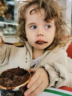 Gezicht op een schattig meisje dat chocolade-ijs eet..