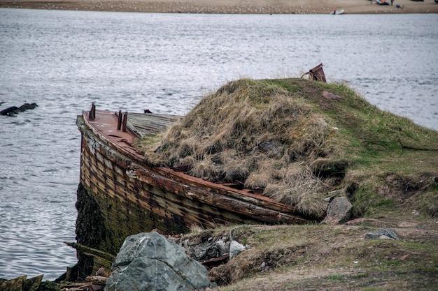 Gezicht op een verlaten schip begroeid met mos