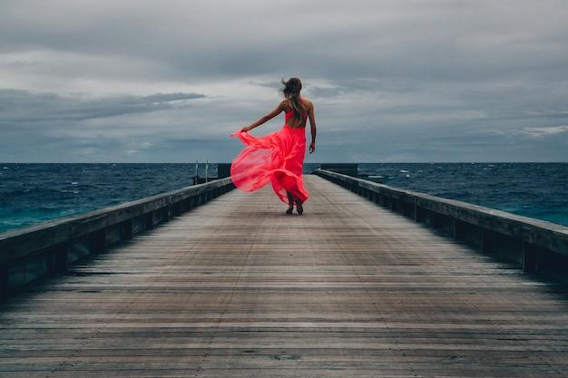 Gezicht op een vrouw in een lange roze jurk die op een winderige dag op de pier loopt