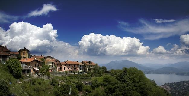 Gezicht op huizen bovenop een berg met uitzicht op een zee omgeven door bergen