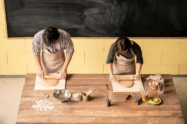 Gezicht op twee jonge hedendaagse zelfstandige pottenbakkers in schorten die bij tafel staan en klei uitrollen met deegrollen