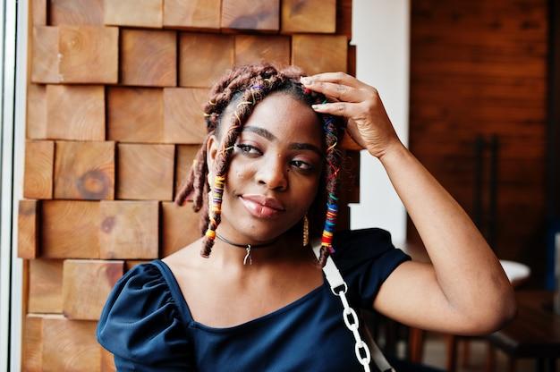 Gezicht portret van mooie afro-amerikaanse vrouw met dreadlocks in café. mooi cool modieus zwart jong meisje binnen.