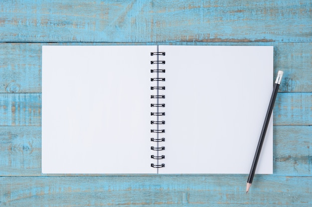 Gezicht schetsboek en potlood op vintage blauwe houten tafel
