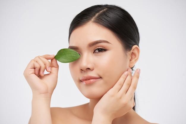 Gezicht van aantrekkelijke jonge vrouw die oog bedekt met groen blad en naar camera kijkt, concept van natuurlijke schoonheid