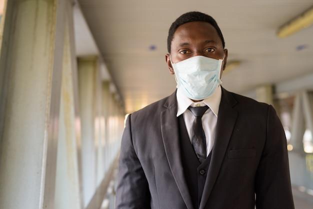 Gezicht van afrikaanse zakenman die masker draagt bij de voetgangersbrug