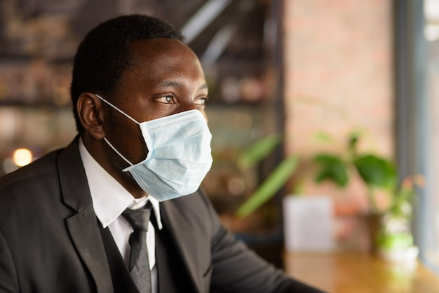 Gezicht van afrikaanse zakenman die masker draagt en binnen de koffiewinkel denkt als nieuw normaal