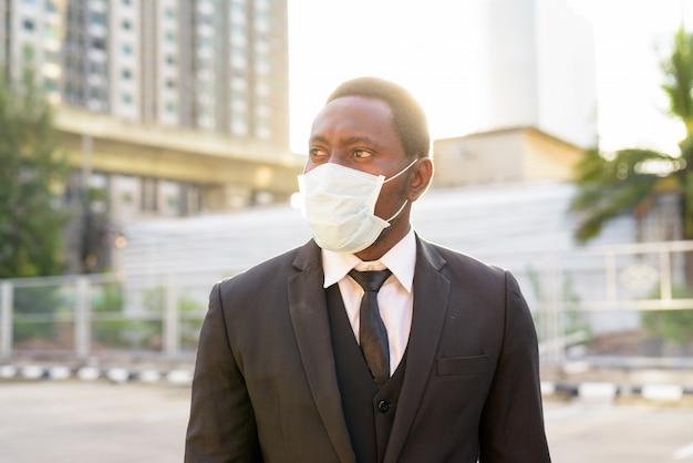 Gezicht van afrikaanse zakenman met masker denken in de straten van de stad