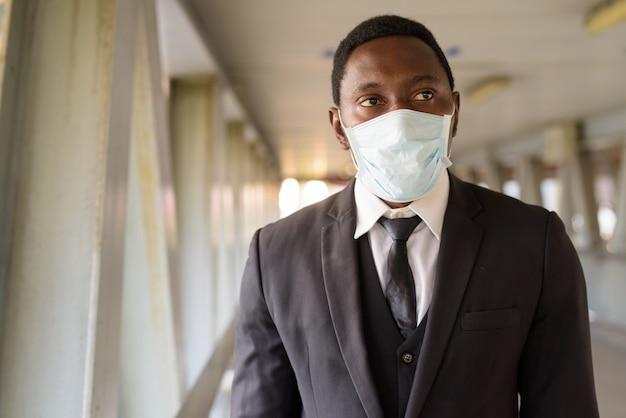 Gezicht van afrikaanse zakenman met masker denken op de voetgangersbrug
