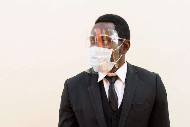 Gezicht van afrikaanse zakenman met masker en gezichtsschild die tegen witte achtergrond denken