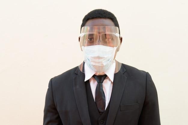 Gezicht van afrikaanse zakenman met masker en gezichtsschild voor bescherming tegen corona virus uitbraak buitenshuis