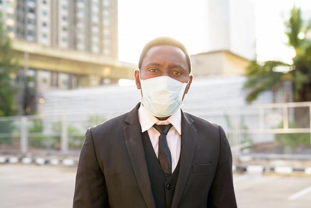 Gezicht van afrikaanse zakenman met masker in de straten van de stad