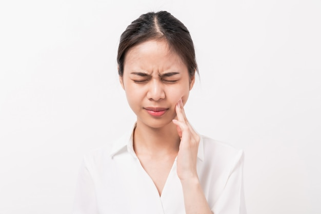 Gezicht van aziatische vrouw, haar vinger raakt haar wang vanwege kiespijn.