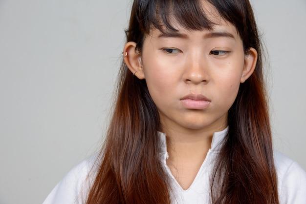 Gezicht van beklemtoonde jonge aziatische vrouw die en neer denkt kijkt