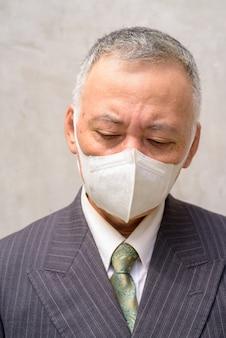 Gezicht van beklemtoonde rijpe japanse zakenman die met masker in openlucht denken