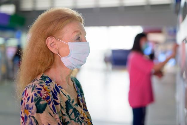 Gezicht van blonde hogere vrouw die met masker kaartje kopen bij het hemelstation