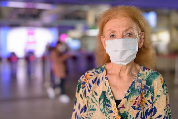 Gezicht van blonde senior vrouw masker dragen en sociale afstand nemen op het sky train station