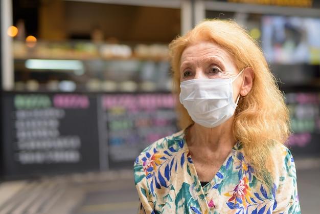 Gezicht van blonde senior vrouw met masker denken in de coffeeshop buitenshuis