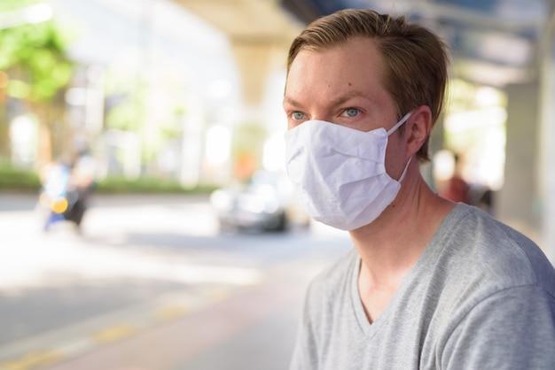 Gezicht van de jonge man met masker te wachten en bij de bushalte te zitten