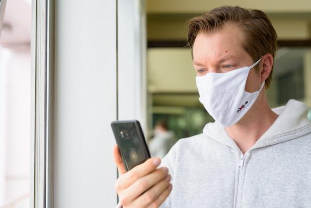 Gezicht van de jonge man met masker via telefoon bij het raam klaar voor sportschool