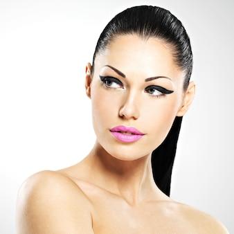Gezicht van de mooie vrouw met maniermake-up. sexy meisje met roze geïsoleerde lippen -